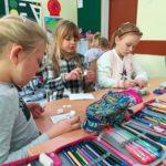 Dzieci kolorują pocztówki.