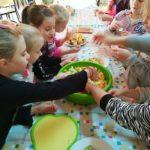 dzieci przydotowują sałatkę owocową