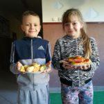 Dzieci prezentuja zrobioną sałatkę i kanapki.
