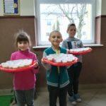 Dzieci trzymają na tacach samodzielnie zrobione soki.