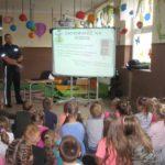 Dzieci słuchają prelekcji policjanta.