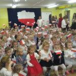 Przedszkolaki machają flagami.