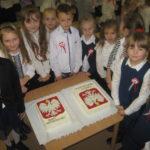 Dzieci wokół tortu z godłem Polski.
