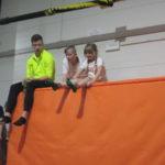 Uczniowie siedzą z trenerem na materacach.