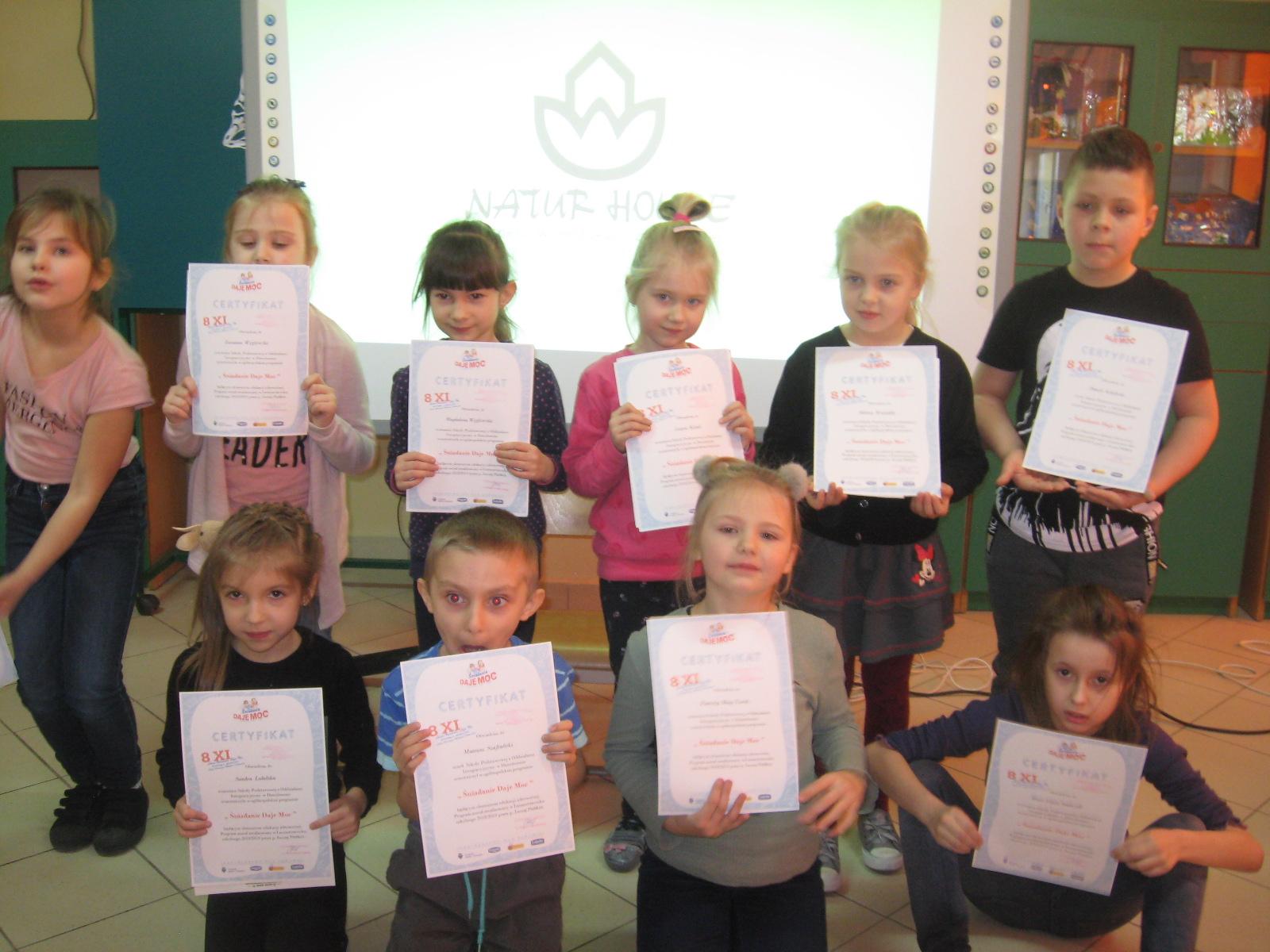 Dzieci prezentują zdobyte dyplomy.