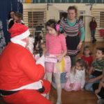 Mikołaj wręcza dziewczynce prezent.