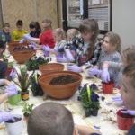 Dzieci sadzą roślinki do doniczek.