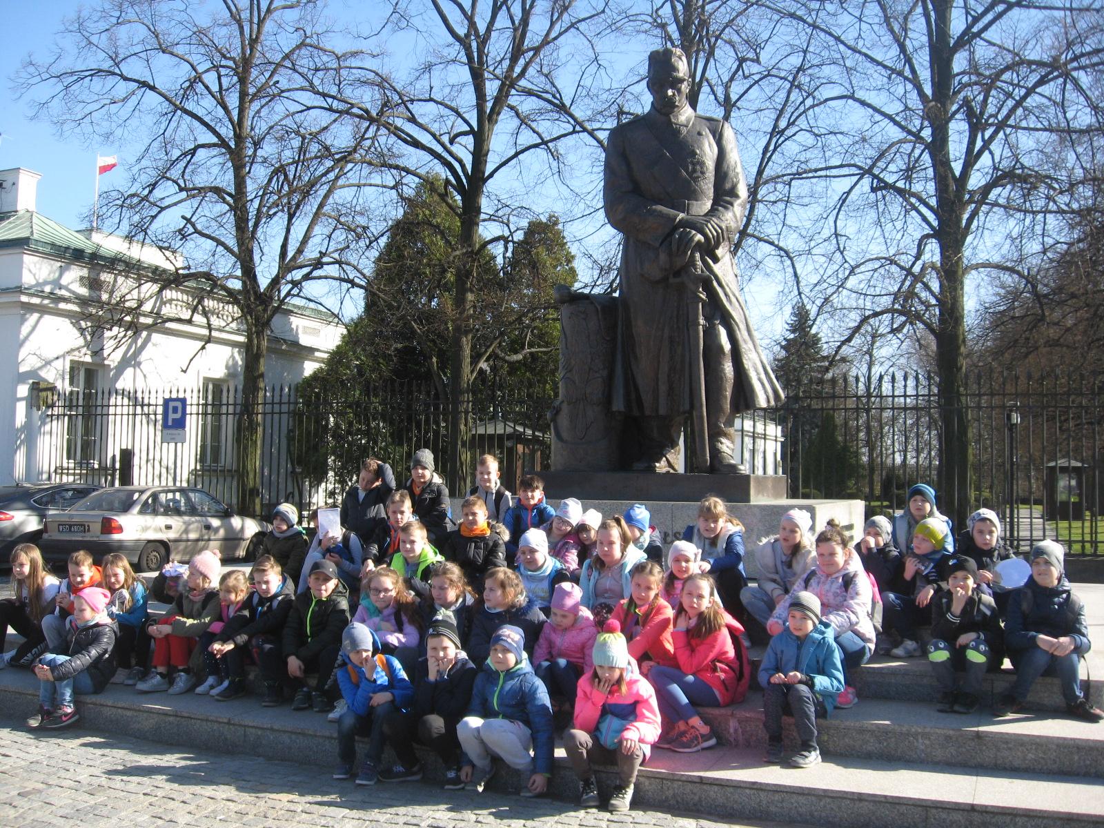 Wspólne zdjęcie przed pomnikiem Józefa Piłsudskiego.