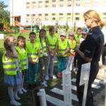 Pani policjantka omawia z dziećmi rolę znaków drogowych.