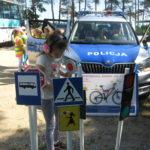 Uczennica ogląda znaki drogowe.