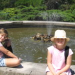 Dzieci odpoczywają obok fontanny.