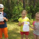 Uczniowie prezentują zawieszki na drzwi