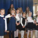 Dzieci ubrane na galowo z biała i czerwoną różą.