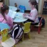 Dziewczynki czytają książki w bibliotece.