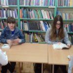Uczniowie czytają książki w bibliotece.