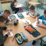Uczniowie prezentują rysują laurki dla Powstańców.