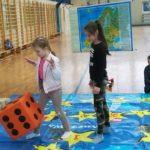 Dziewczynki rzucają dużą kostką do gry.
