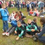 Chłopcy siedzą na trawie w oczekiwaniu na wyjście.