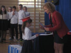 Pani Dyrektor wręcza dyplom pierwszoklasiście.