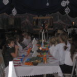 Uczestnicy siedzą przy wigilijnym stole.