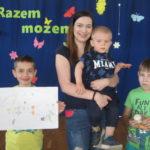 Rodzice z dziećmi prezentują herby rodzin.