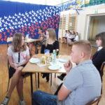 Zaproszeni goście oraz wykonawcy siedzą za stołami.