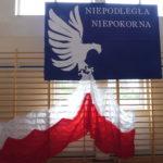 Dekoracja - orzeł trzyma w szponach biało-czerwoną flagę.