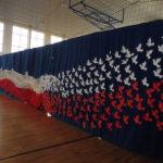 Dekoracja -biało- czerwone gołębię wznoszą ku niebu biało-czerwoną flagę