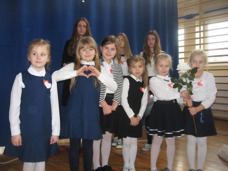 Dziewczynki z białą i czerwoną różą.
