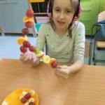 dziewczynka prezentuje przyggotowanie owocowe szaszłyki.
