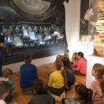 Przewodnik w muzeum rozmawia z dziećmi.