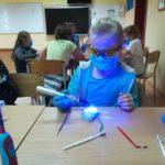 Uczennica używa lampy do plombowania.