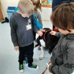 Dzieci głaszczą psa.
