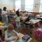 Uczniowie rozdają prace konkursowe.