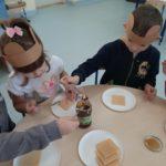 Dzieci smakują miód.