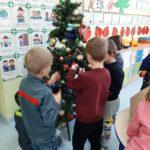 Dzieci ubierają choinkę.