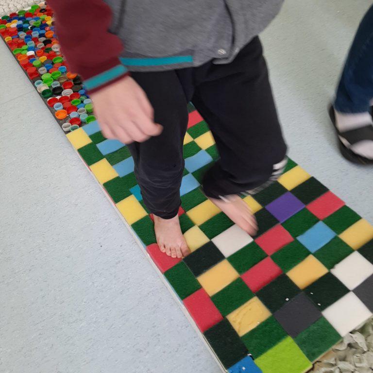 Dzieci spacerują po ścieżce sensorycznej.