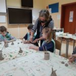 Dzieci wykonują prace z gliny.