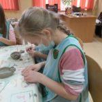 Dzieci wykonują miseczkę z gliny.