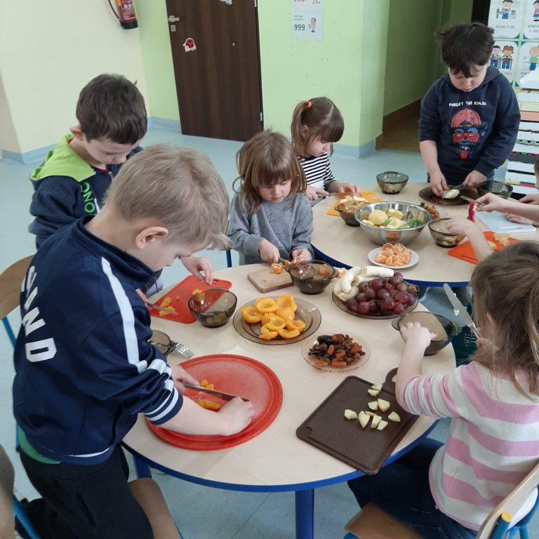 Dzieci przygotowują sałatkę owocową.