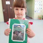Dziewczynka prezentuje fotografię psa.