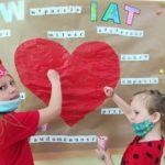 Uczniowie klasy pierwszej wykonują plakat - dziecko o wielkim sercu.