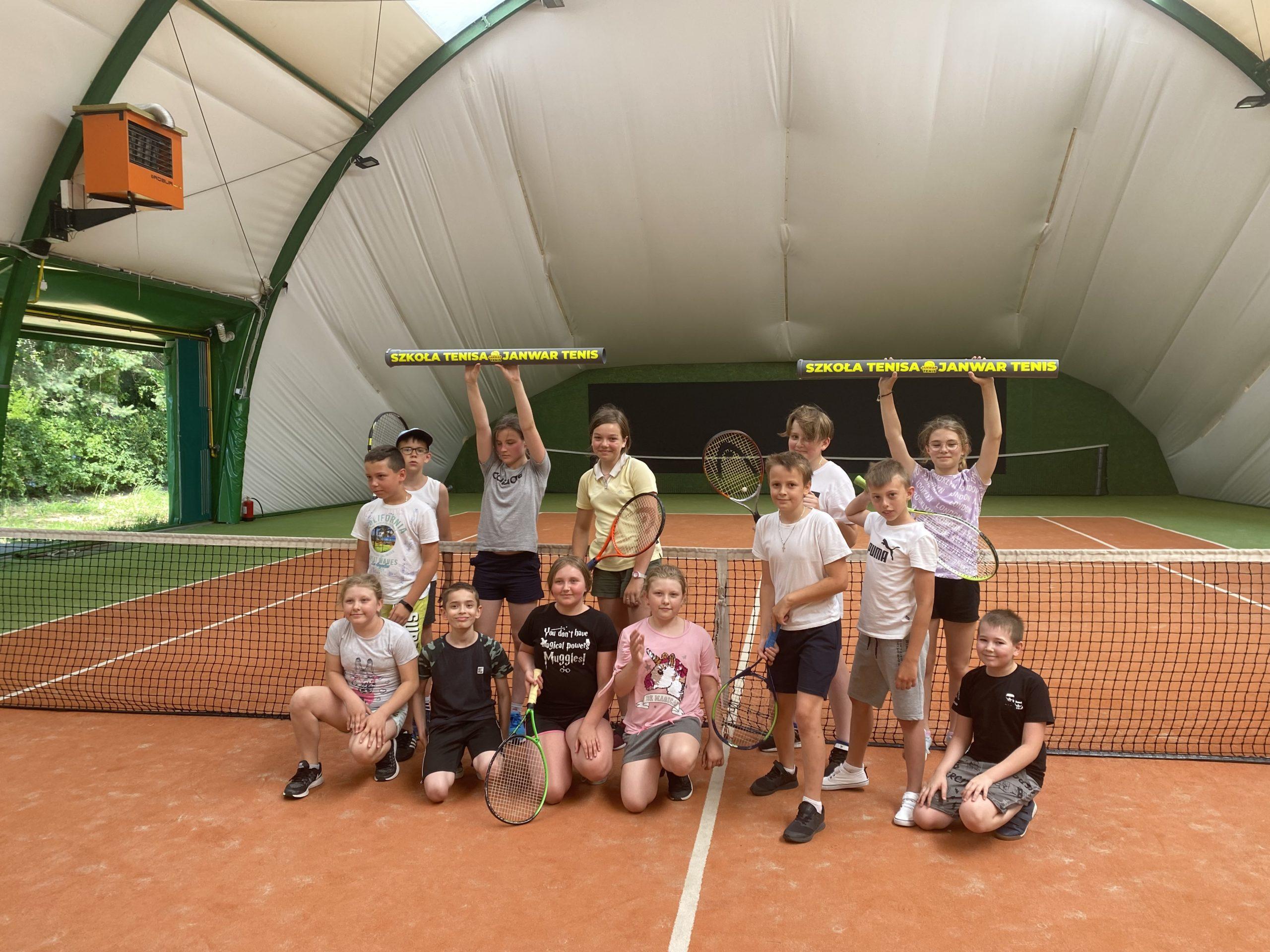 Dzieci grają na korcie tenisowym.